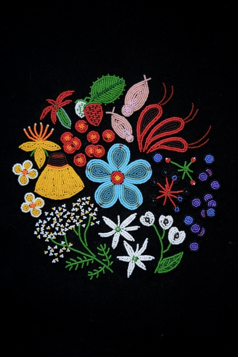 artwork of colourful beaded flowers, leaves and fruit on a black backgorund