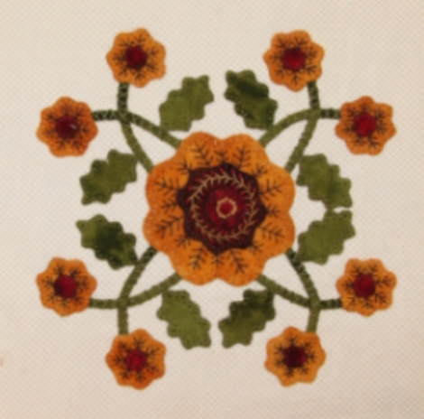 applique of a large central flower surrounded by vines and leaves with eight small flowers