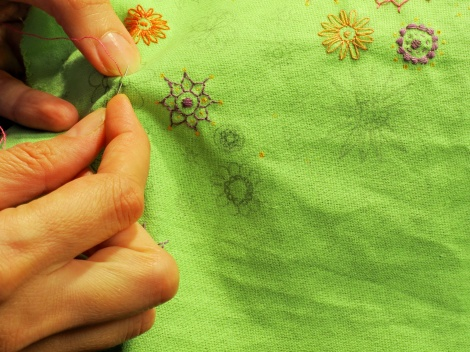 Hands embroider abstract patterns of flowers on a green cloth.