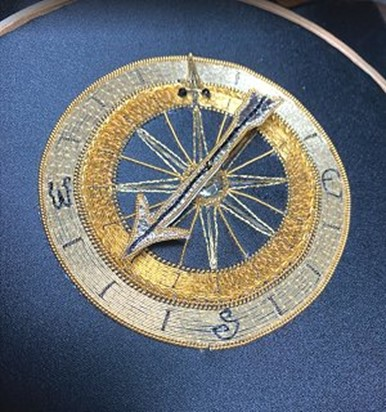 gold and silver compass on blue fabric