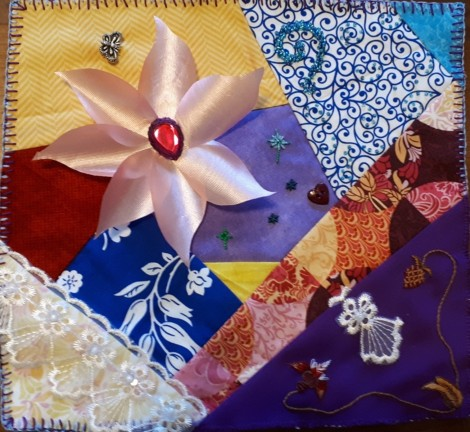 crazy quilt block with large pink flower